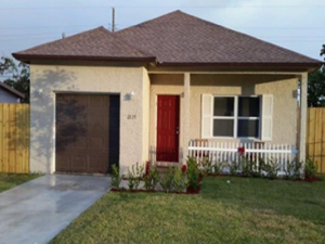 Beige house with red door, brown roof and picket fence in south Florida
