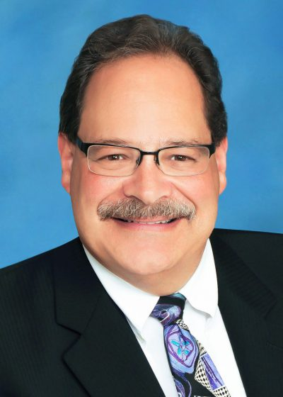 Greg Ross in a dark suit and colored tie over a blue background