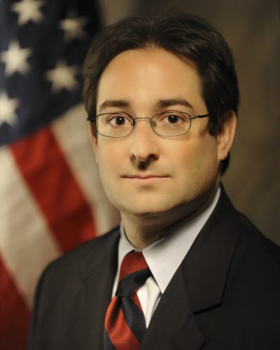 Jordan in a dark suit, red tie, with a US flag in the background