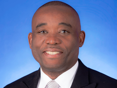 Commissioner Jean Monestime in a dark suit on a blue background