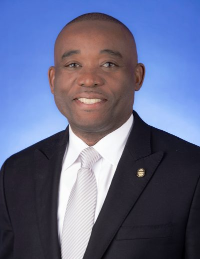 headshot of Commissioner Monestime in a dark suit and white tie