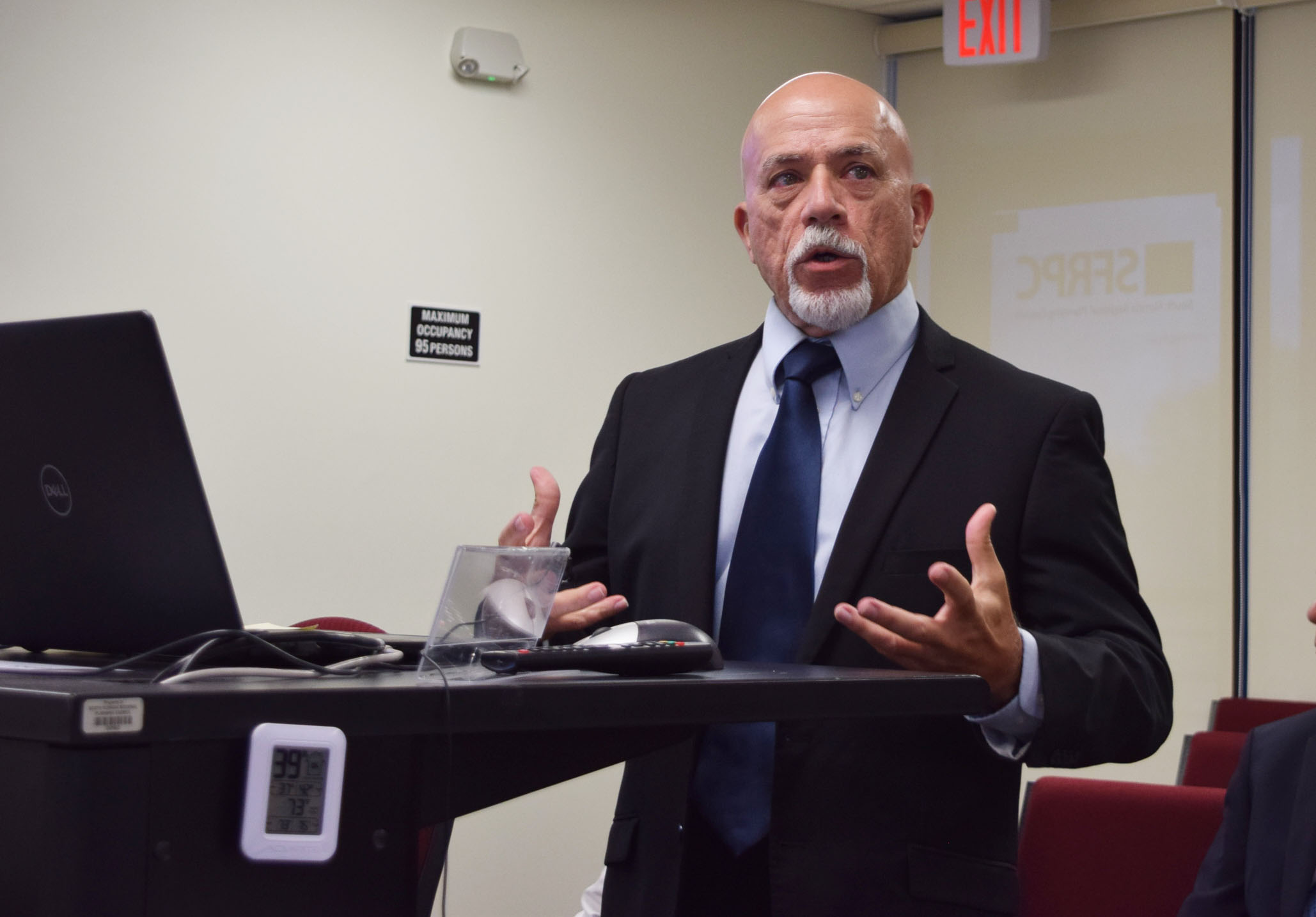 South Florida Regional Planning Council Deputy Director Manny Cela in a blue suit presenting an update with a laptop