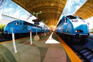 2 blue Tri-Rail trains on a railroad track at a stop