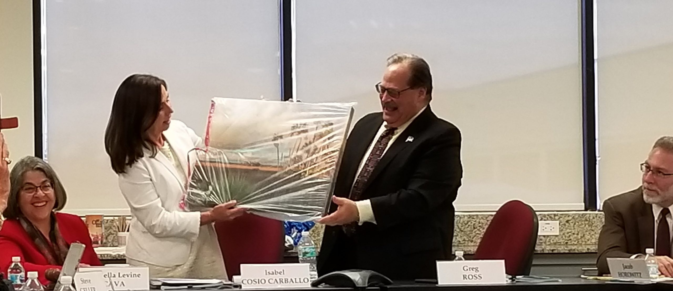 isabel carballo handing former chair Greg Ross a painting of a beach in South Florida